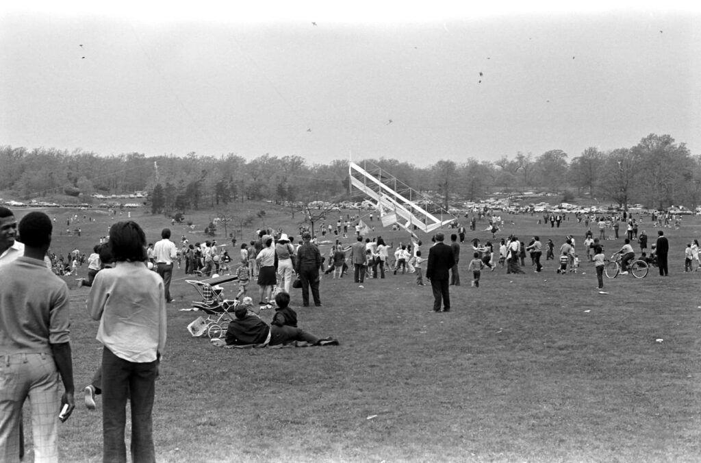 A huge kite at an angle above a crowd of people on a grassy field in Franklin Park.