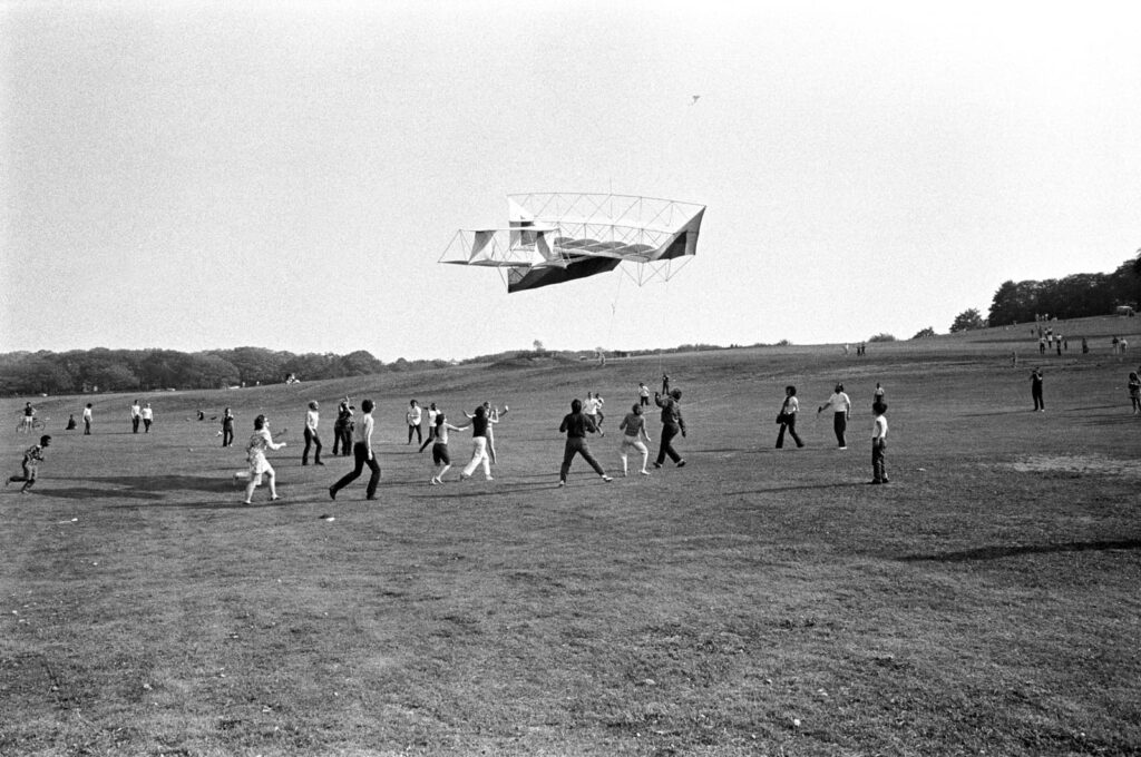 A group of people walking on a large expanse of grass with a large kite overhead.