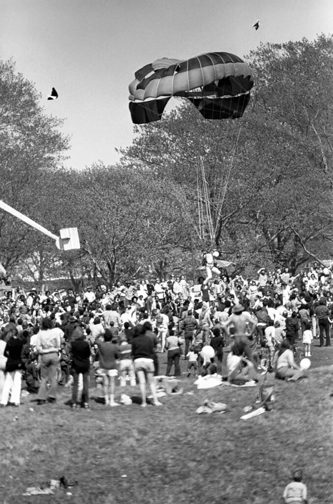 A man with a parachute descends onto Franklin Park in a crowd during the 1971 Great Boston Kite Festival.