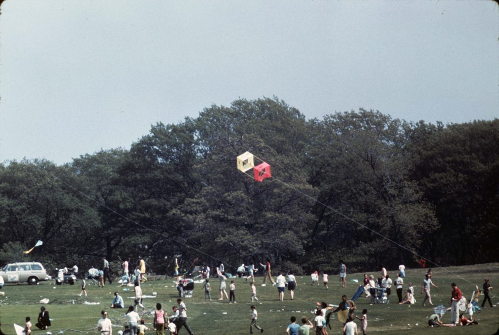 A yellow and red box kite flying above a grassy field bordered by trees in Franklin Park, Boston with lots of people sitting and standing on the grass.