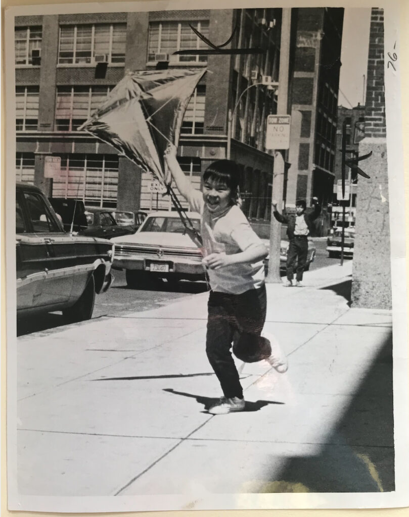 A child runs down a sidewalk in Boston's Chinatown flying a kite behind him in 1969.