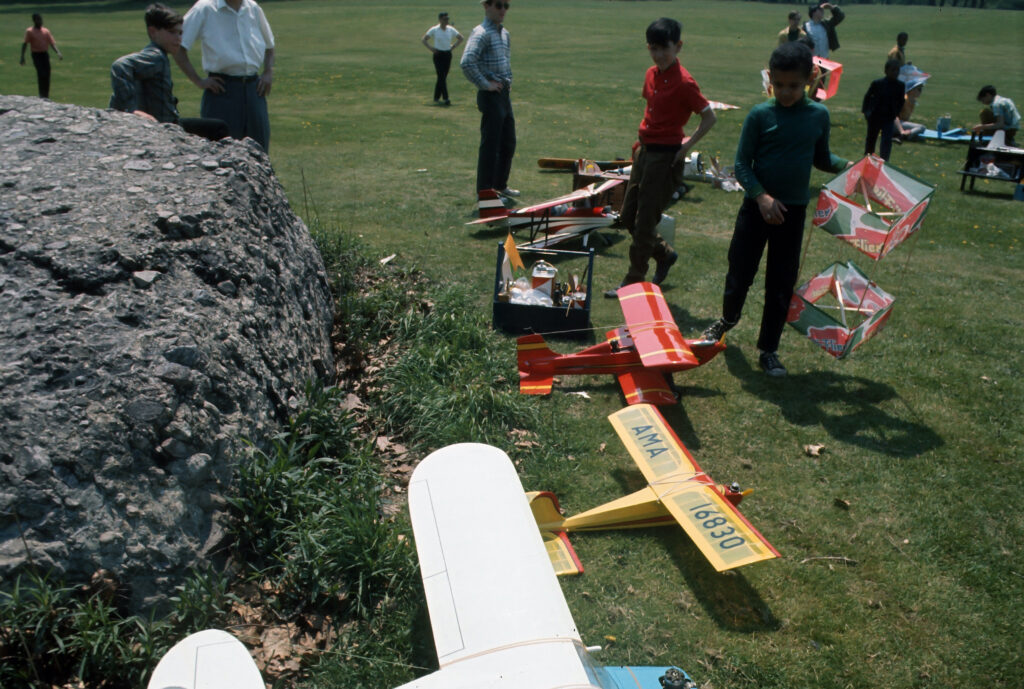 A group of adults and children stand around radio controlled model airplanes parked on the grass next to a large boulder.