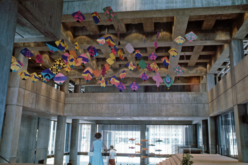 Dozens of kites suspended in the atrium of Boston City Hall in 1969. Here, an adult and a child are walking underneath the kites.