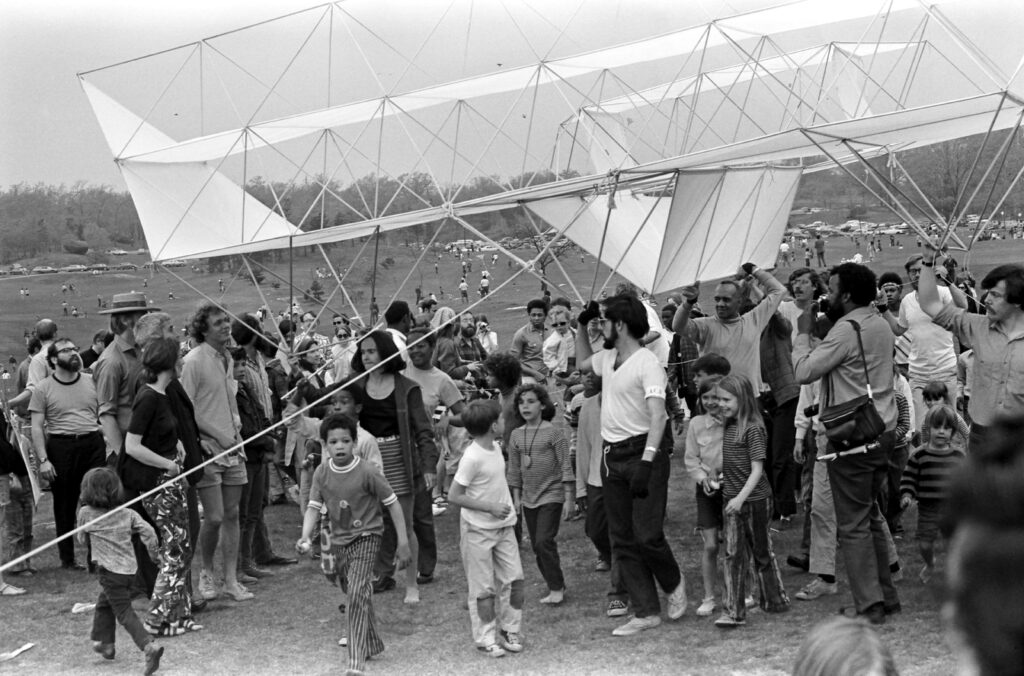 A large group of adults and children carry a huge kite above their shoulders. 1969 was a time of social reckonings and upheaval, both nationally and in Boston.